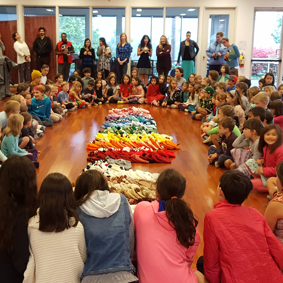 Many children sitting in a large room around a pile of colorful hats