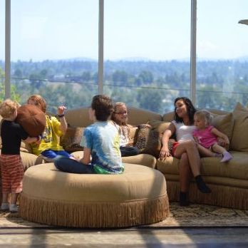 Children and adults sitting on couches in front of large windows