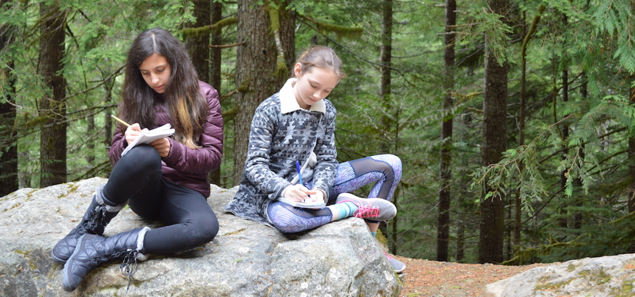 Middle Schoolers Sitting On A Rock Reading