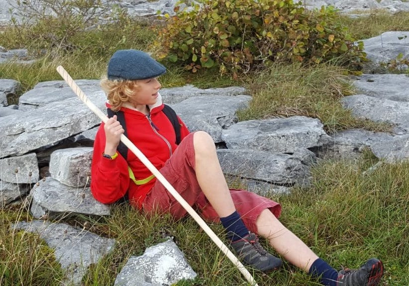 A young man relaxing against a rock holding a walking stick