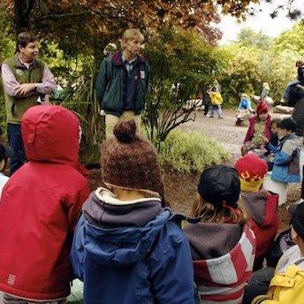 Children listening to a man speak outdoors